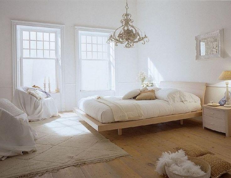 helles, weißes Schlafzimmer mit Dielenboden und Sessel bedeckt mit Stoff