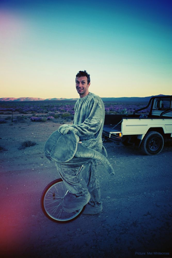 Chris Martin on the set of new Coldplay music video. For those wondering, he can ride the unicycle in that suit.