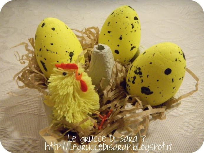 Centrotavola con una scatola delle uova,  piena di pagliuzze di carta, uova colorate e un pulcino