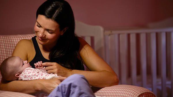 mamá con bebé en brazos al lado de la cuna, sujetándole la mano al bebé