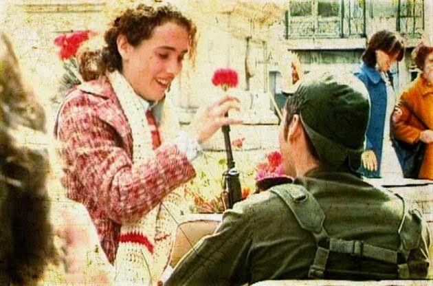 Jovem mulher oferecendo um cravo a militar no dia