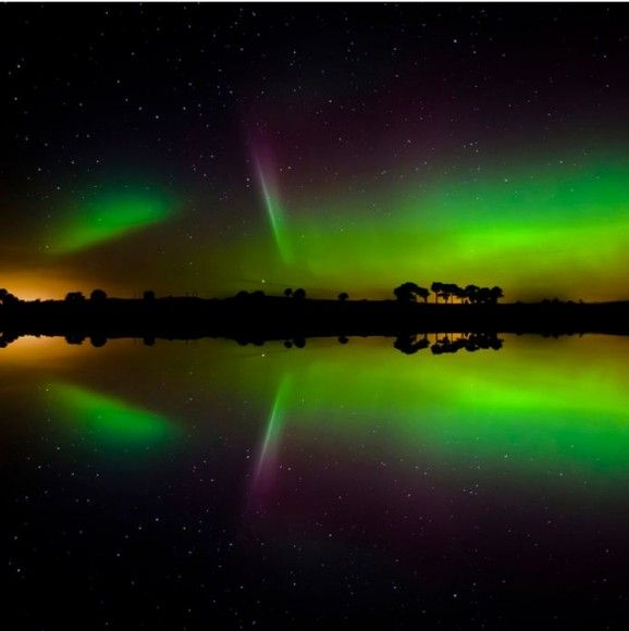 The Northern Lights over Kilmany, Scotland, reflect in a body of water. Credit: Corinne Mills