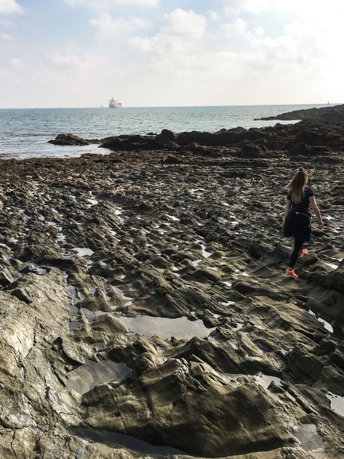 Walking over the rock pools at low tide during autumn in Cornwall