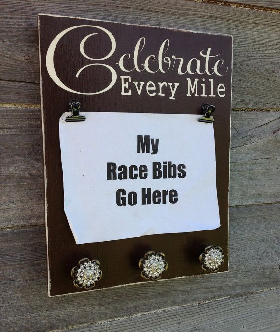 The perfect combination of rustic and bling! This sign is made for holding race bibs and displaying ribbons or medals. The bibs are held by antique looking clips. The medal holders are a sturdy metal knob accented with bling. They are heavy and do give the sign some weight. The paint combination shown is vanilla with expresso brown. The edges are slightly distressed. The sign is sealed with an acrylic sealant for forever beauty.  This sign measures 10 x 14 on a standard pine board. The edges…