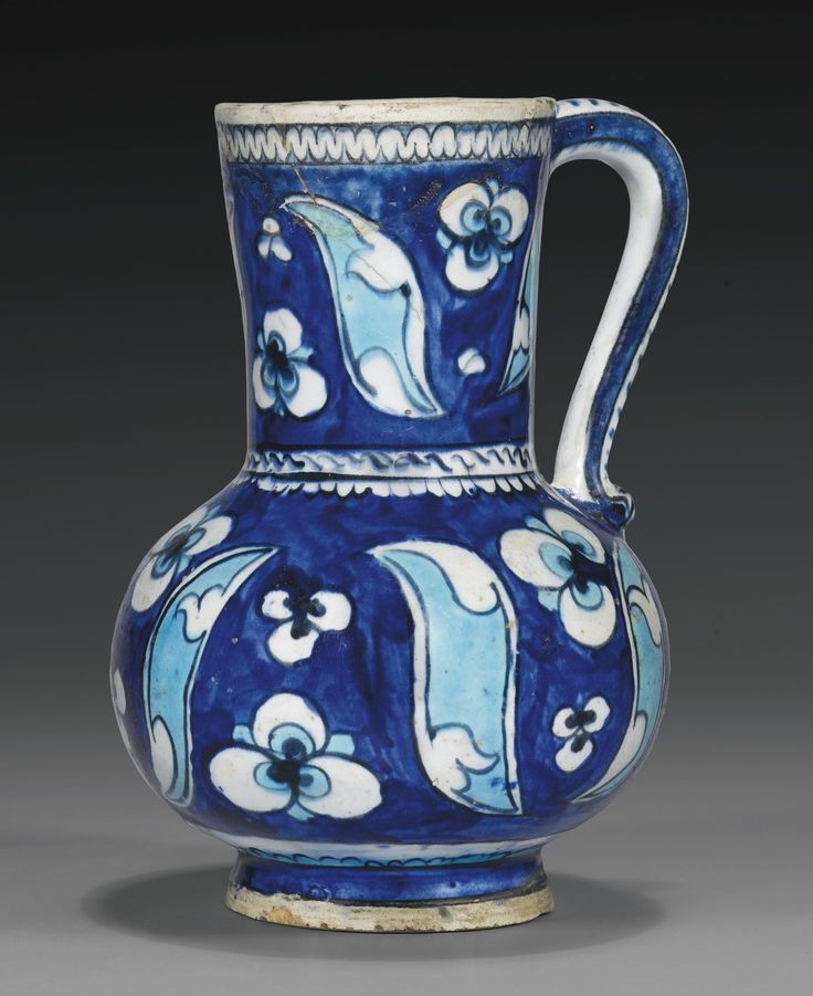 AN IZNIK BLUE AND TURQUOISE POTTERY JUG, TURKEY, CIRCA 1530-50 of baluster form with a cylindrical, slightly flaring neck and curved handle, painted with stylised cintamani motifs and saz leaves in turquoise and white with black outline under an underglaze cobalt blue background, the handle with cobalt blue stripes  20cm. height.