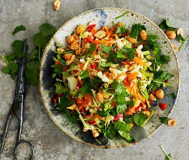 """Fräsch råkostsallad med smaker som påminner om thailändska papayasalladen """"Som Tam"""". Strimla vitkål, riv morot och blanda med den goda dressingen på chili, vitlök, socker, lime och fisksås. Avsluta med koriander och torrostade jordnötter."""