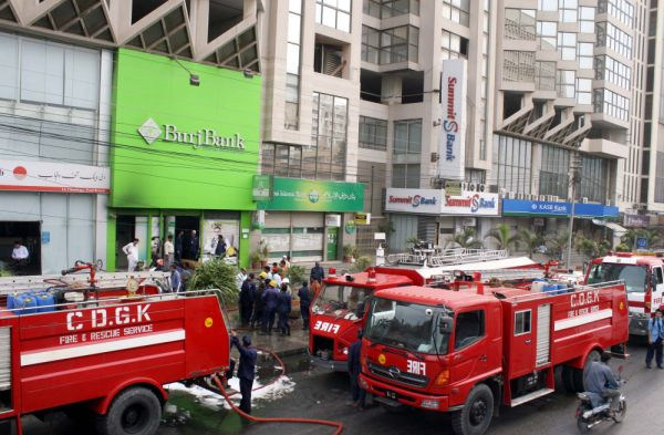 Firefighters extinguish fire on burning building of a local bank after fire broke out incident due to electricity short-circuit at I.I.Chandrigar road in Karachi on Wednesday, July 11, 2012.