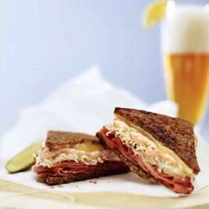 Reuben sandwich with German ingredients such as Westphalian ham, sauerkraut, and Tilsiter cheese, served on pumpernickel bread.