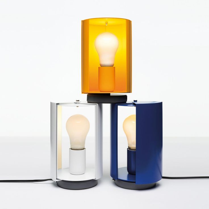 PIVOTANTE À POSER Table lamp with a cylindrical body, open on two sides, on which two diffusers rotate and allow the opening and closure of the lighting beam, in order to adjust the light in a direct or indirect way. Base in steel painted in matt grey, body in rolled metal sheet painted in white, yellow or blue. Switch on cable.