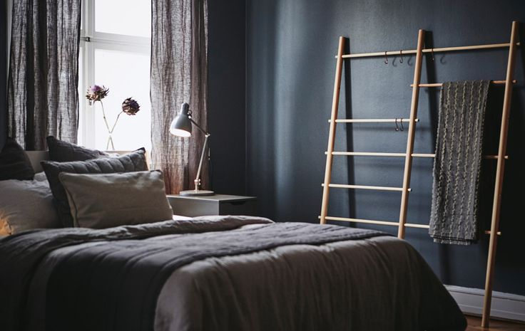 A dark-walled bedroom with a window, a bed, a bedside table and a blanket ladder.