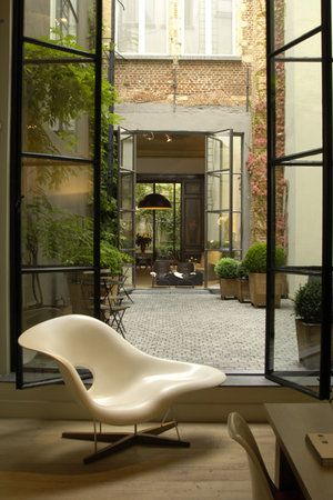 Nice courtyard, especially the rough concrete finish punched opening for the industrial-looking glass folding doors