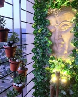 A large embossed Buddha wall art decked with artificial vines and golden lights make this balcony extremely calm and relaxing. Green Blacony  by Takeaway Interiors