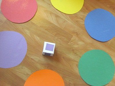 This is a little game we made for our preschoolers to have fun working on color recognition...    First we made a little cube and put a different color on each side - red, yellow, blue, green, orange, and purple. Then we cut out 6 large circles