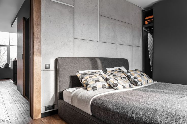 In this modern bedroom, there's a concrete accent wall with embedded lighting, while a dark bed frame and headboard match the dark grey floor-to-ceiling closet that runs along the wall.
