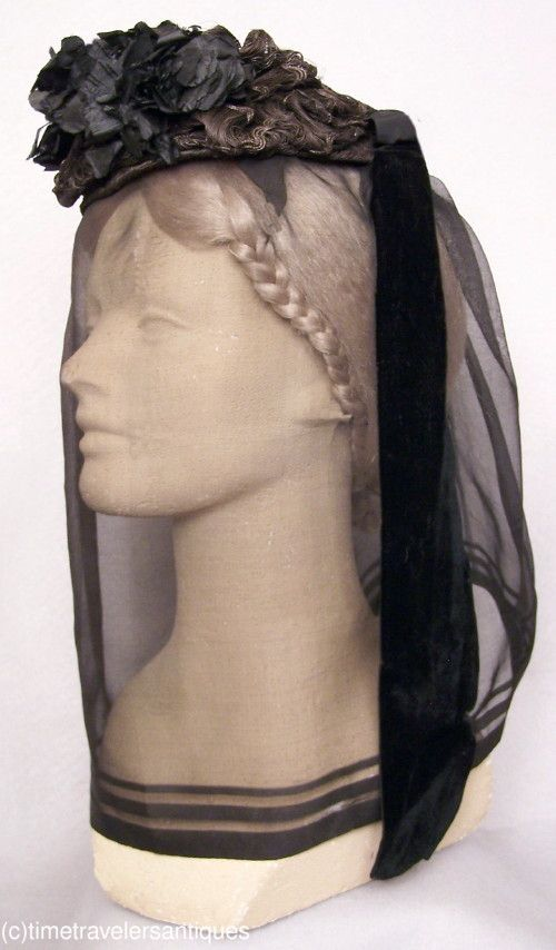 An original circa 1865 to 1875 lady's fanchon style woven horsehair and braided straw gimp mourning bonnet with a spray of black cloth flowers at the front. Silk velvet streamers, a silk drawstring lining with a wired buckram foundation, and a black silk mourning veil. ... from eBay ... photo 1