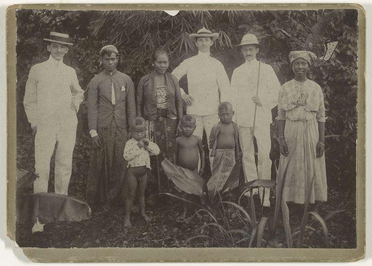 Anonymous | Pa in Suriname, Anonymous, 1909 | Foto met zes volwassenen en drie kinderen tussen bananenplanten in Suriname. Het gezelschap bestaat uit drie blanke volwassen mannen, vermoedelijk Nederlanders, een Javaans gezin, bestaande uit een man en een vrouw en drie kleine kinderen, en een Creoolse vrouw. Op de achterkant een opschrift.