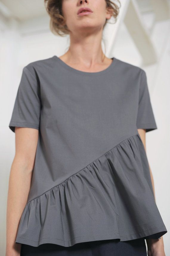 This playful gray cotton blouse has round neckline, short sleeves and gathered diagonal flounce.