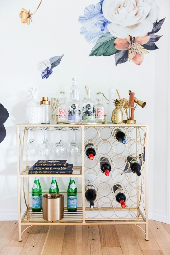 This home bar is gorgeous. I love the bright colors and the floral wallpaper. Bar cart design at it's best right here!