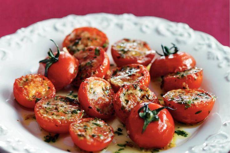 Gegrilde tomaten Verwarm de ovengrill. Snijd de tomaten horizontaal doormidden. Leg de tomatenhelften met de snijkant naar boven op een bakplaat. Rasp de kaas en strooi erover. Pers de knoflook en roer samen met de kruiden door de olie. Breng op smaak met peper en zout. Besprenkel de tomatenhelften met de kruidenolie en zet ze ca. 10 min. onder de gril. Neem ze uit de oven en leg voorzichtig de bovenkant (met de steelaanzet) schuin op de onderkant van de tomaat.