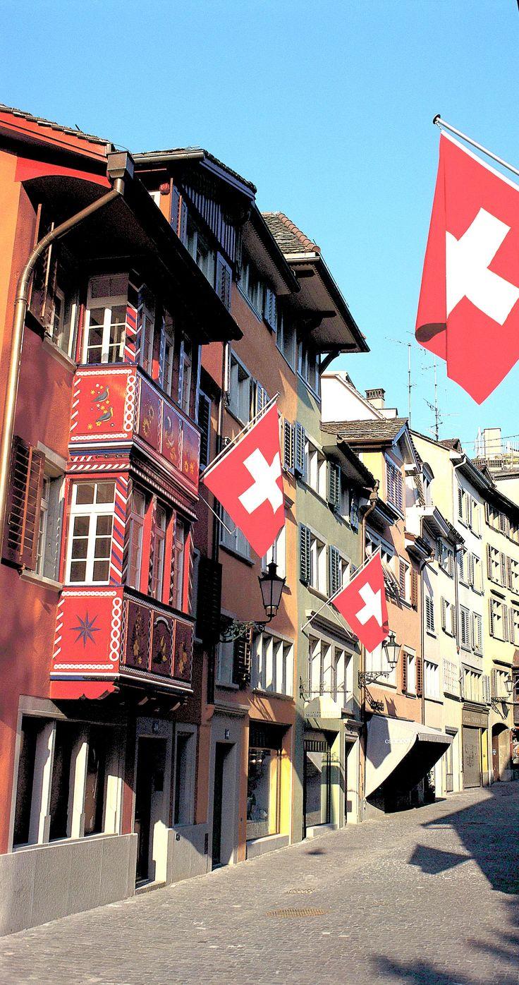 Schweizer Flaggen und bunte, kunstvoll bemalte Häuser in einem Züricher Straßenzug. #verschweizert #Schweiz