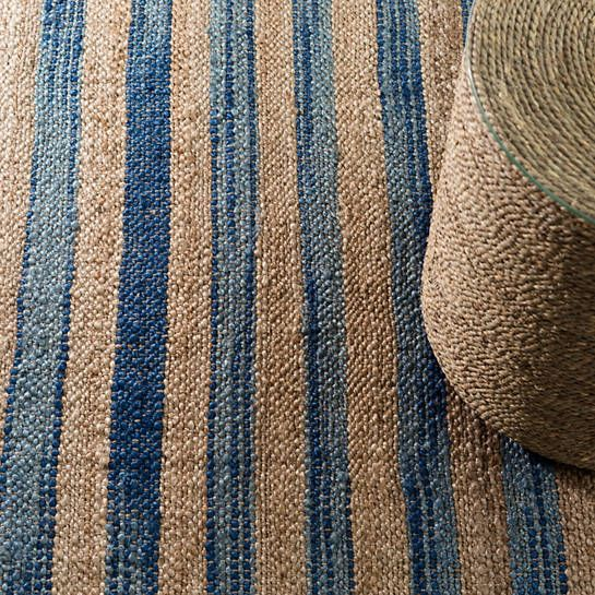 This hardworking natural jute and azure blue striped rug brings a welcoming, happy feeling to your home.
