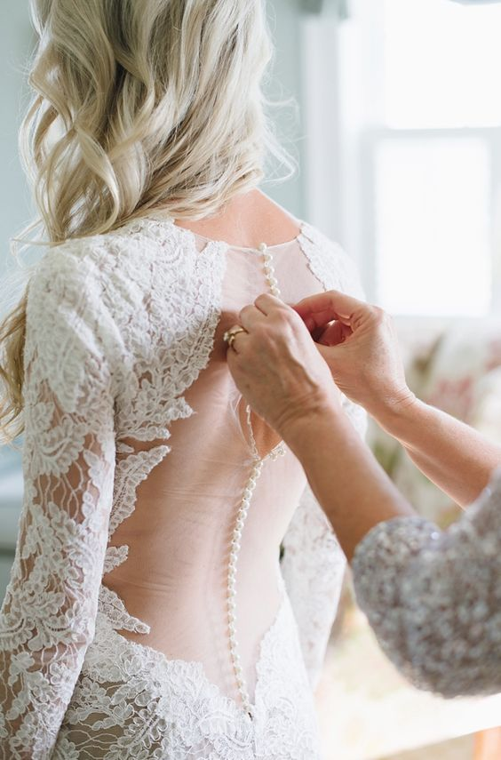 Classic long-sleeve embroidered lace button down back wedding dress; Featured Photographer: Natalie Franke Photography