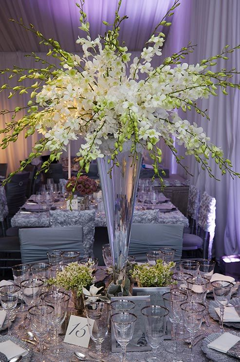 This tall glass centerpiece is bursting with blossoming