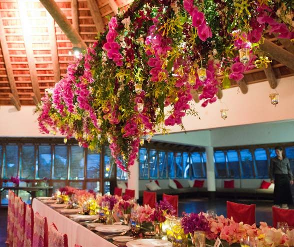 The lush arrangement hanging over the head table creates a feeling of dining in a tropical jungle.
