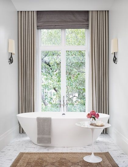 gorgeous. I <3 bathrooms that don't loook like a bathroom. Gorgeous grey curtains, beautiful freestanding tub, rug, side table. Perfect!