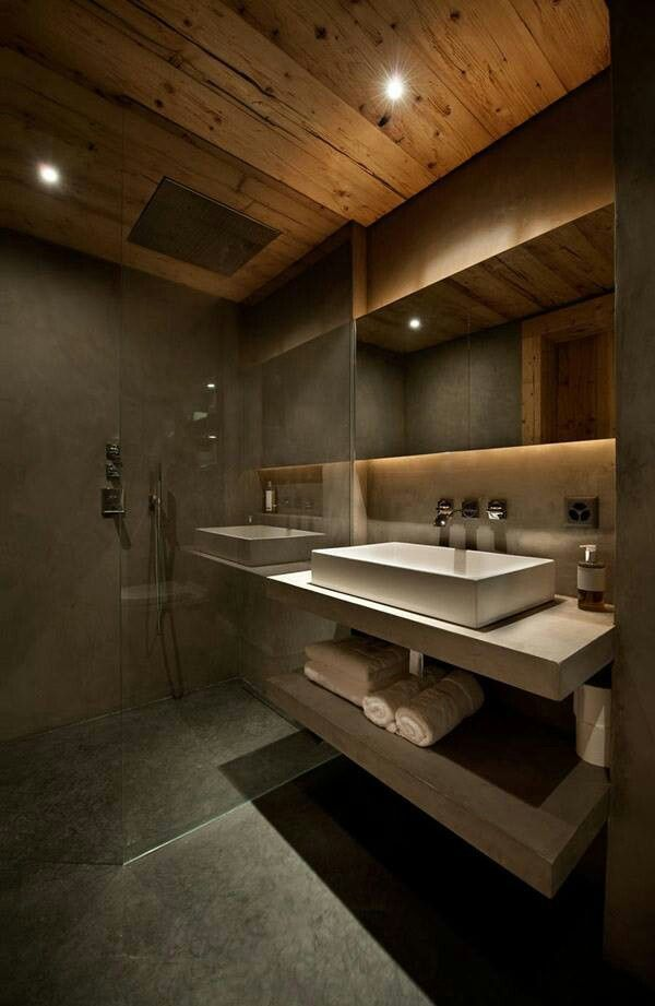 Dramatic modern bathroom with cement walls and vanity, warmed up by the wood treatment on the ceiling.