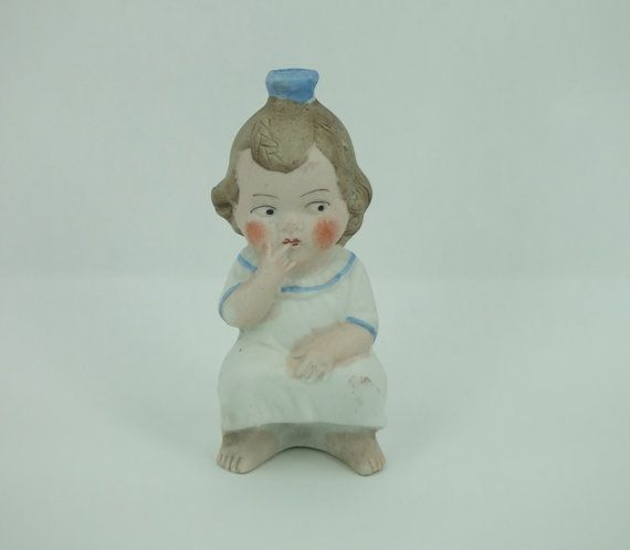An Antique hand painted German bisque squirter bottle of a naughty girl squatting. The top opening should accommodate a rubber squirter bulb, and when