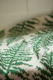 Adorned with fern-inspired leaves floating in the wind, this generously sized fanciful afghan adds a modern touch of nature to your home. The afghan is knit flat in stockinette stitch while the garter stitch border is picked up and knit along the sides. The Fronds Afghan uses a chart for the stranded motif portion of the pattern.