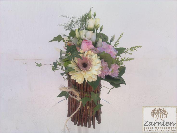 Ρουστίκ σύνθεση τραπεζιού σε βάση από κλαδιά με άνθη και φυλλώματα σε ροζ, λευκό, φούξια.  Στο ίδιο μοτίβο μπορεί να γίνει το νυφικό μπουκέτο, οι λαμπάδες και γενικά όλη η διακόσμηση του γάμου σας κάνοντας τον μοναδικό