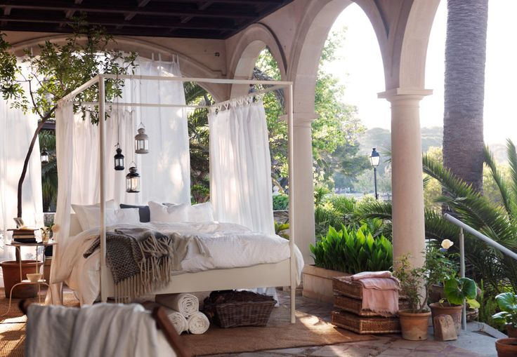 A large white bed with with lamps and curtains hanging around it on a grand balcony surrounded by palm trees