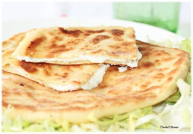 Le khachapuri est un pain plat géorgien très moelleux grâce à la présence de yaourt avec de multiples variantes. Ici une version en forme de galette fourrée à la mozzarella, fêta, ricotta et yaourt grec.