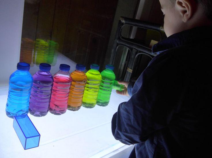cubes translucides multicolores et bouteilles arc en ciel sur table lumineuse