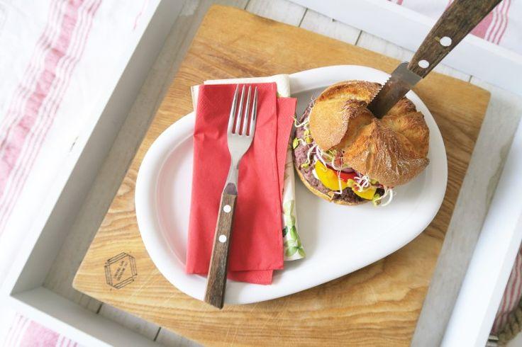 burger z fasoli  Składniki:      bułka żytnia lub orkiszowa (najlepiej z pełnego ziarna),     warzywa do burgera (kiełki rzodkiewki, pomidor, sałata, ogórek, cebulka),     mozzarella,     olej rzepakowy,     BURGERY:         fasolka czerwona (z puszki/ zwykła, wcześniej namoczona i ugotowana),         jajko,         2 ząbki czosnku,         1 cebula,         pół szklanki kaszy jaglanej,         ulubione przyprawy.