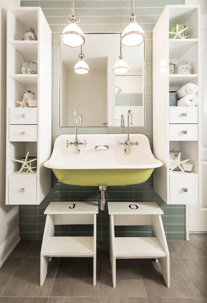 Kidsu0027 Bathroom Features Tall And Slim Floating Display Cabinets Mounted On  Gray Glass Tiles In Grid Formation Flanking Mirror Over Yellow Trough Sink  ...