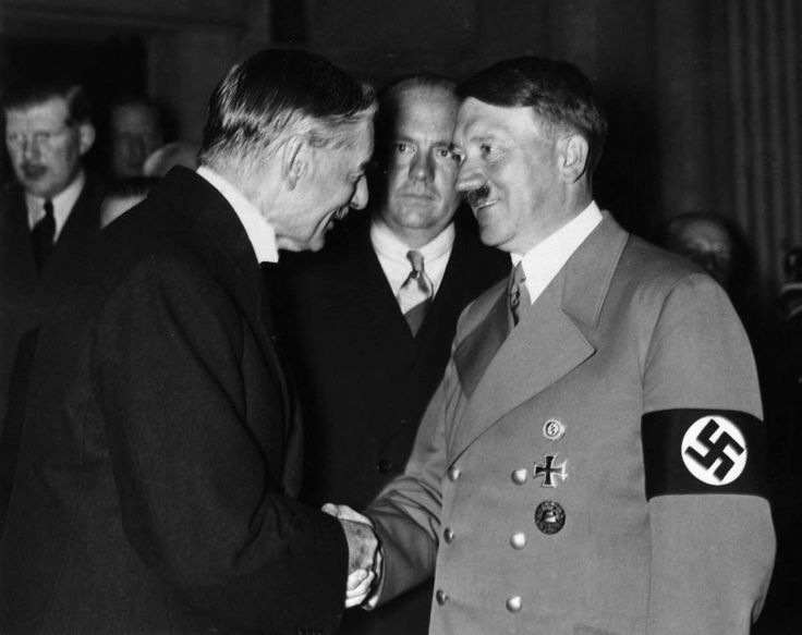 """Hitler greets the British PM, Neville Chamberlain, in 1938. Chamberlain led the European chorus to appease Hitler by agreeing to his expansionist plans. The Munich Agreement served Hitler with Czechoslovakia on a silver platter. Chamberlain was naive enough to proclaim that the agreement had brought """"peace in our time."""""""