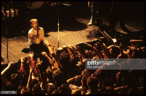Members of the audience reach up to David Bowie as he kneels at the front of the stage while performing with Tin Machine at Paradiso, Amsterdam, Netherlands, 24th June 1989.