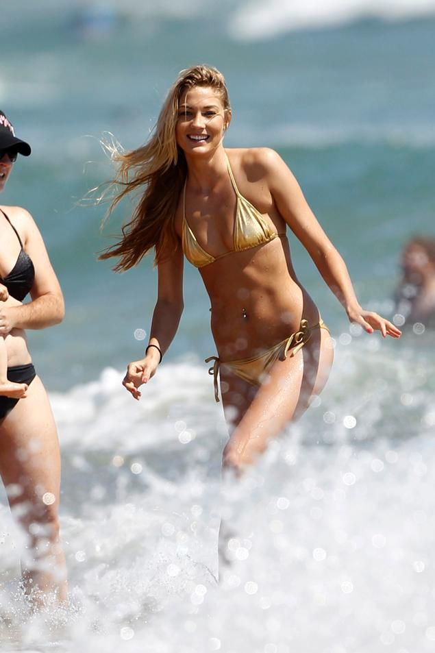 Phelps back into the water - his gorgeous galpal Megan Rossee in a skimpy gold bikini. The leggy model showed she looks every bit as good in gold as her Olympic record-breaking beau, who has hung up his Speedo at aged 27 with a record 18 gold medals.