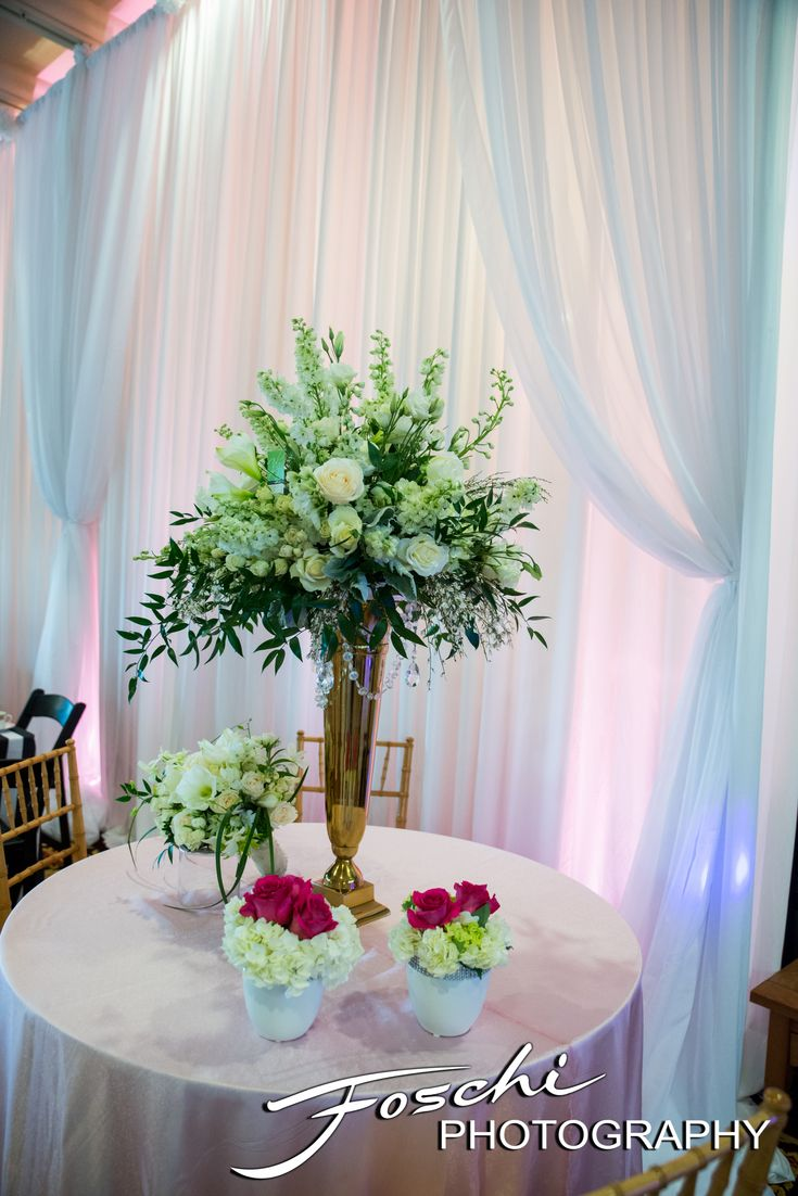 An elegant wedding centerpiece of luxurious white flowers and greens accented by a wall of graceful drapery. Foschi Photography.