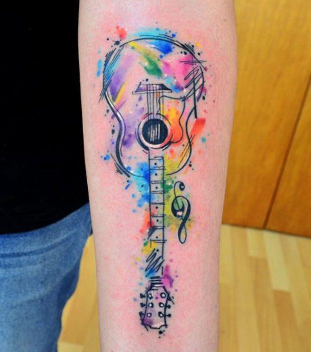 Tatouage aquarelle sur le bras une guitare acoustique