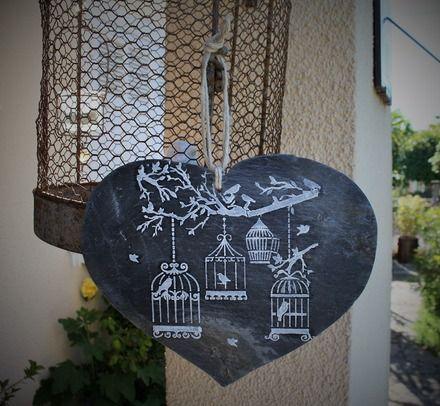 Cœur en ardoise découpé dans une ancienne tuile de toiture  avec en décor des cages à oiseaux suspendues sur des branches  , réalisées au pochoir avec de la peinture solide  - 20668917