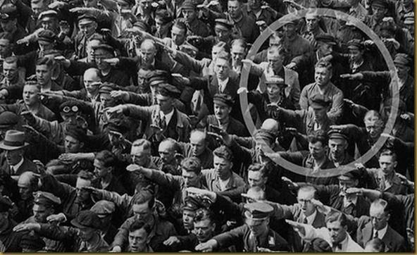 Story behind the picture is online, just search for August Landmesser.  He refuses to follow the crowd and give the Nazi salute.
