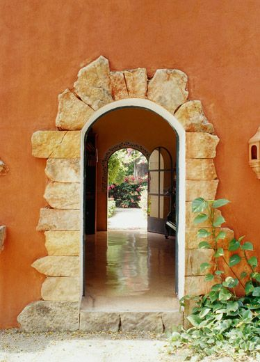 Rich earth tone walls surrounded with coarse stone makes dramatic entrance