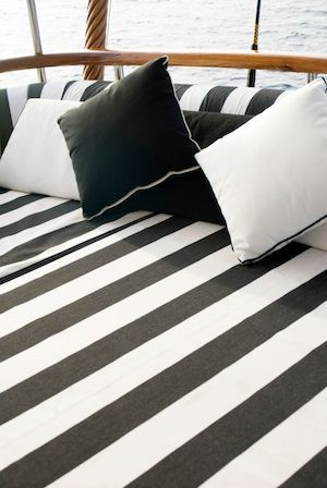 Black and white striped marine grade upholstery for boat exterior - daybed, cushions, & seating  Raeline Upholstery can achieve this look for your boat - contact us at www.raelineupholstery.com.au #boatdesign