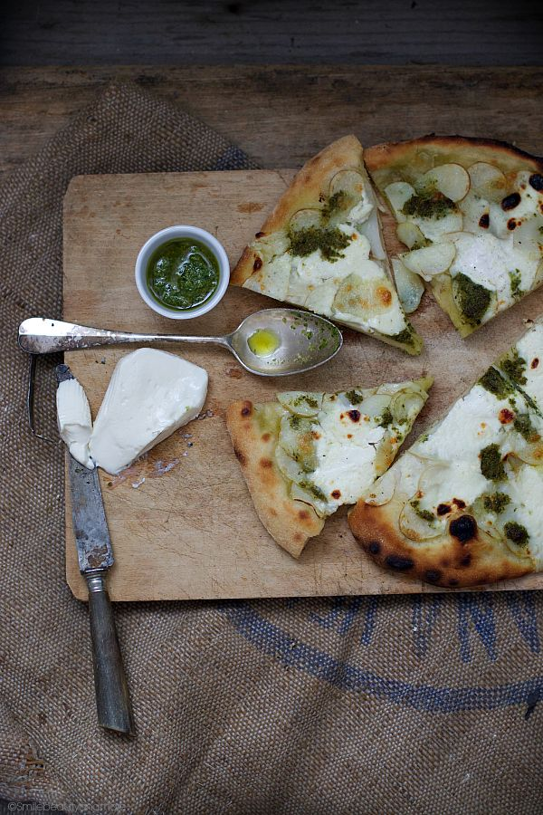 white pizza with potatoes, pesto and soft cheese