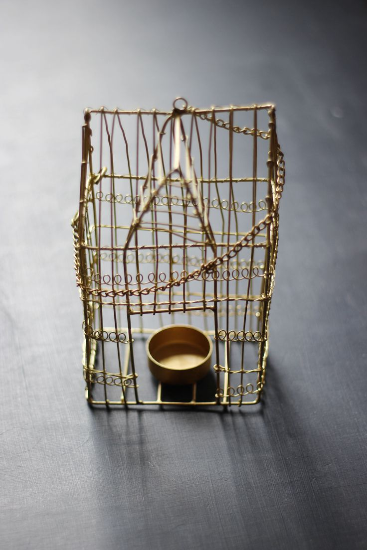 This #golden #wire #cage is in the shape of a house and it holds a tea-light inside http://www.aprilandthebear.com/home-accessories/gold-tealight-birdcage