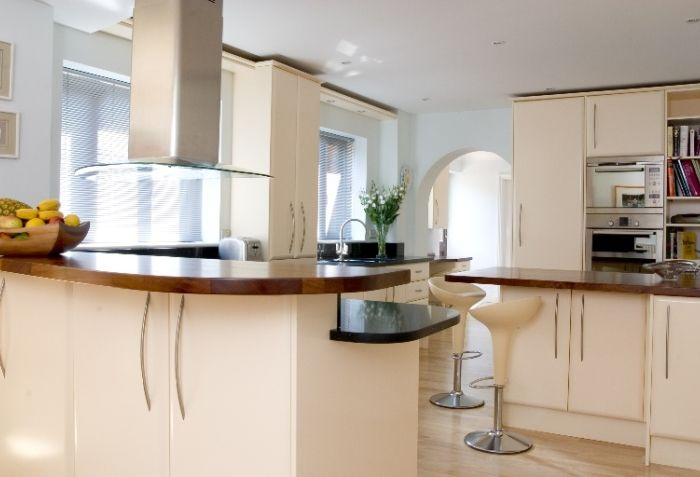 Contemporary kitchen from Anthony Mullan furniture. Spray painted curve doors with a mixture of solid Iroko and stone tops.